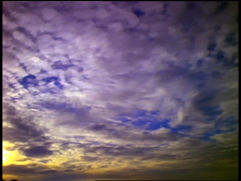 low angle wide shot time lapse clouds moving in blue sky from day to dusk - day to dusk stock videos & royalty-free footage