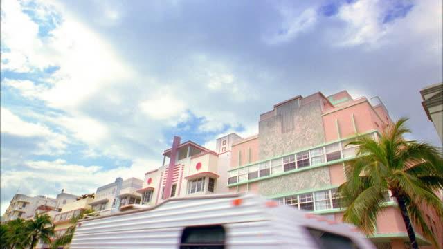 low angle wide shot time lapse clouds passing over buildings / miami beach, florida - オーシャンドライブ点の映像素材/bロール