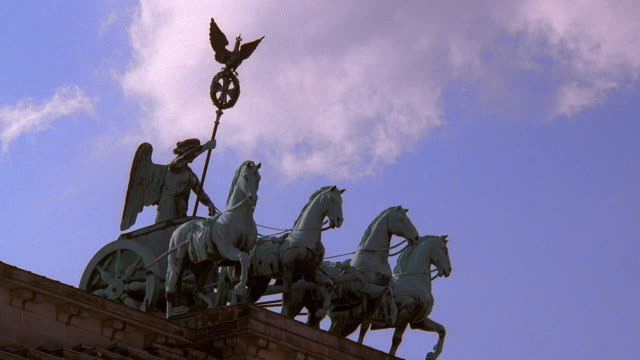 Low angle wide shot time lapse clouds rolling over chariot statue (Quadriga) on top of Brandenburg Gate / Berlin, Germany