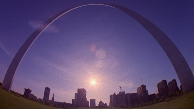 Low angle wide shot time lapse clouds rolling over Gateway Arch with St. Louis skyline and sunset in background / Missouri