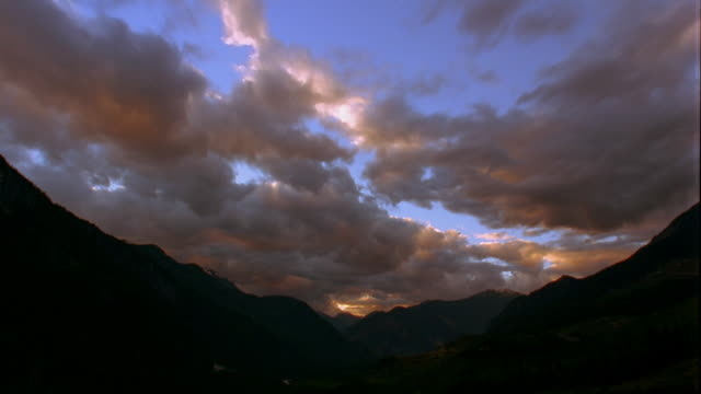 Low angle wide shot time lapse grey clouds with orange sunlight in blue sky over mountains at sunset / British Columbia