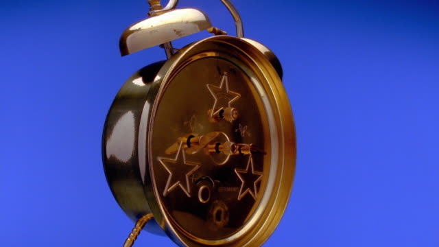 low angle wide shot time lapse hands moving on rotating alarm clock with blue background - man made object stock videos & royalty-free footage