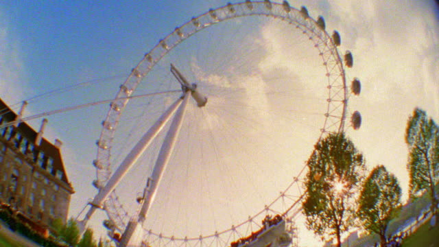 low angle wide shot time lapse millennium london eye ferris wheel turning with clouds moving in sky in background / england - 2001 stock videos & royalty-free footage