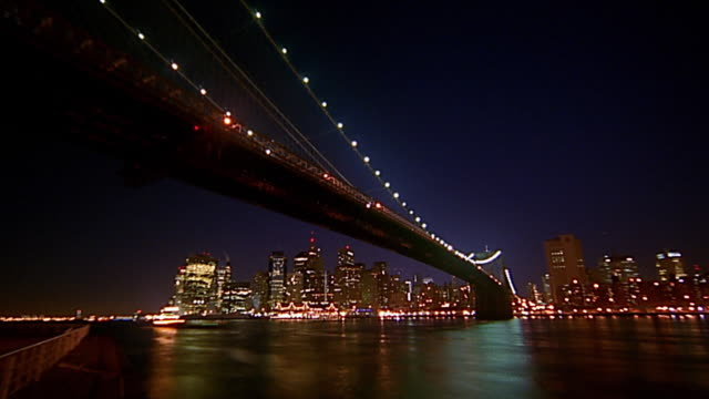 low angle wide shot time lapse night to dawn beneath brooklyn bridge / lower manhattan skyline in background - new york harbor stock videos & royalty-free footage