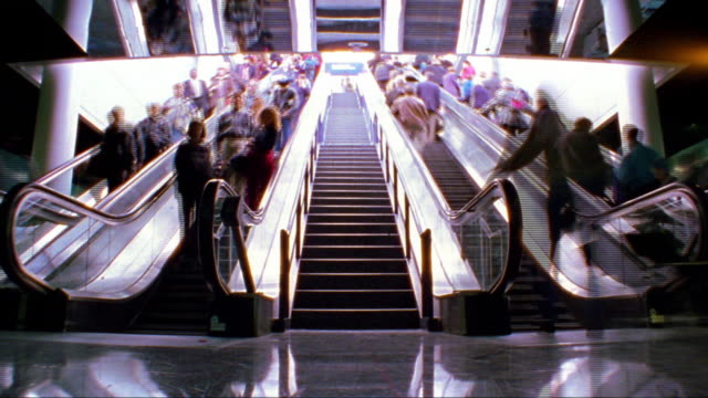 vídeos de stock, filmes e b-roll de overexposed low angle wide shot time lapse people on escalators + stairs in grand central station / nyc (flash frames) - superexposto