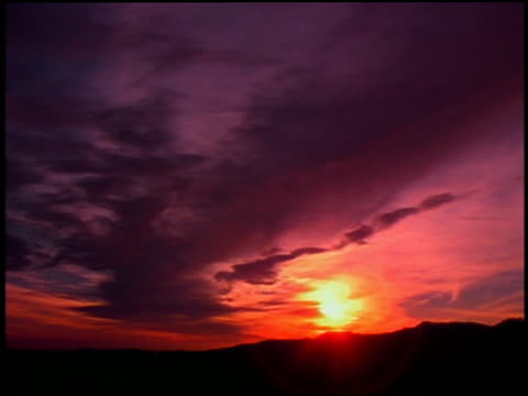 low angle wide shot time lapse pink clouds and sunset over silhouetted mountains - low angle view stock videos & royalty-free footage