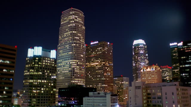 low angle wide shot time lapse skyscrapers in downtown los angeles at night - 点灯・消灯点の映像素材/bロール