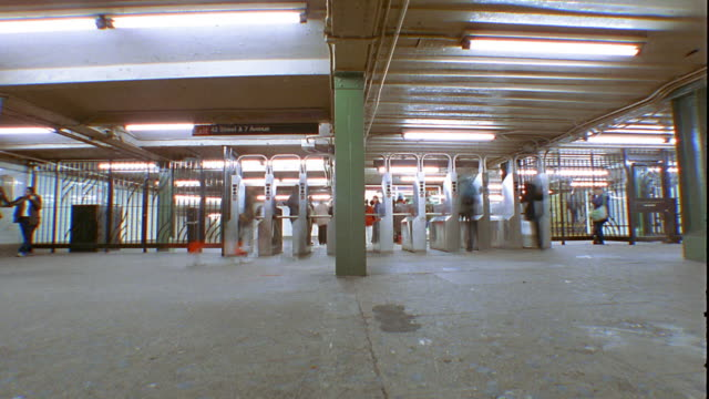 low angle wide shot time lapse subway passengers entering and exiting station through turnstiles / new york city - turnstile stock videos & royalty-free footage
