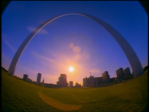 low angle wide shot time lapse sunset behind gateway arch with st. louis skyline in background / people in park / missouri - jefferson national expansion memorial park stock videos & royalty-free footage