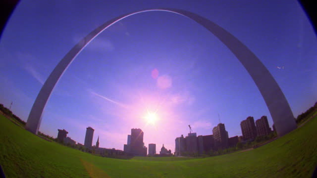 low angle wide shot time lapse sunset behind gateway arch with st. louis skyline in background / people in park / missouri - arch architectural feature stock videos and b-roll footage