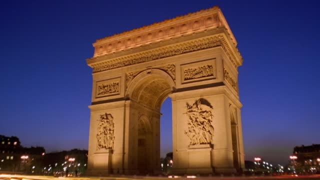vidéos et rushes de low angle wide shot time lapse traffic driving past arc de triomphe at night / paris - arc élément architectural