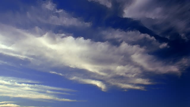 Low angle wide shot time lapse white wispy clouds in blue sky / San Fernando Valley, Los Angeles, California