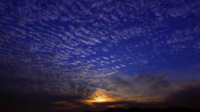 low angle wide shot time lapse wispy cloud cover moving in blue sky over horizon at sunset - 1 minute or greater stock videos & royalty-free footage