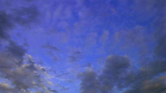 low angle wide shot time lapse wispy clouds darkening in blue sky - wispy stock videos & royalty-free footage