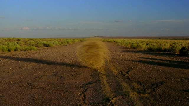 low angle wide shot tumbleweeds rolling across dirt road in desert / holbrook, arizona - rolling stock videos & royalty-free footage