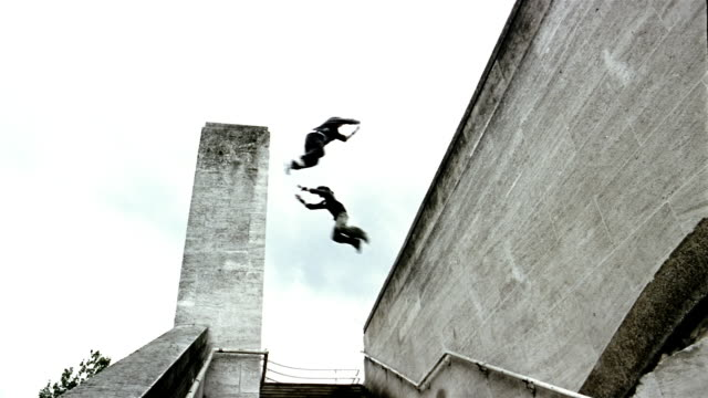Low angle wide shot two freerunners jumping to opposite walls