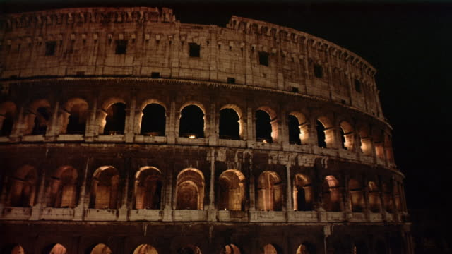 Low angle wide shot view of the Colosseum illuminated at night / Rome