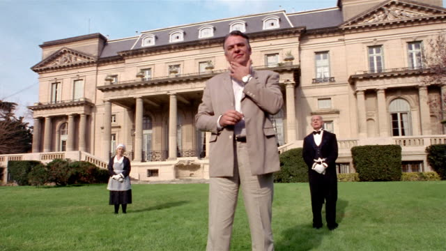 low angle wide shot wealthy man waiting on lawn in front of mansion with servants / walking back to mansion - chin stock videos and b-roll footage