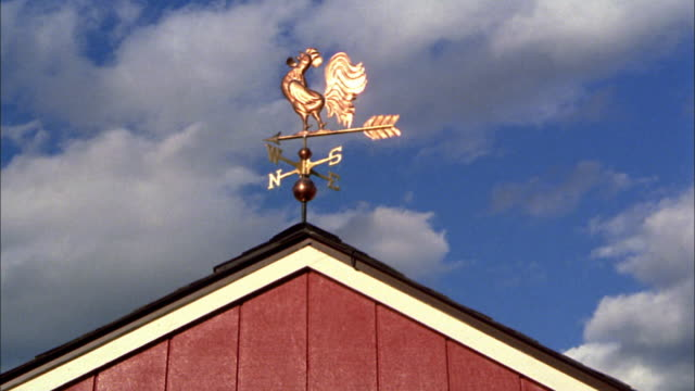 low angle wide shot weather vane spinning on top of barn with clouds in background / new england - arrow symbol stock videos & royalty-free footage