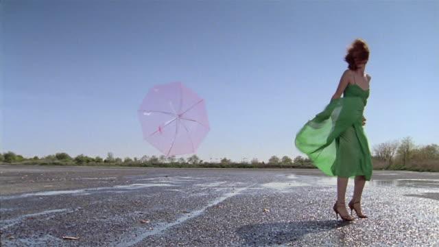 low angle wide shot woman carrying umbrella in windstorm / umbrella flying away - ドレス点の映像素材/bロール