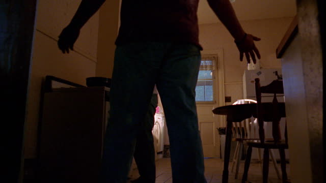 Low angle wide shot woman cooking, man enters kitchen yelling at and threatening woman
