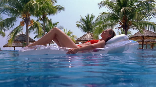 Low angle wide shot woman floating on raft in pool with palm trees in background