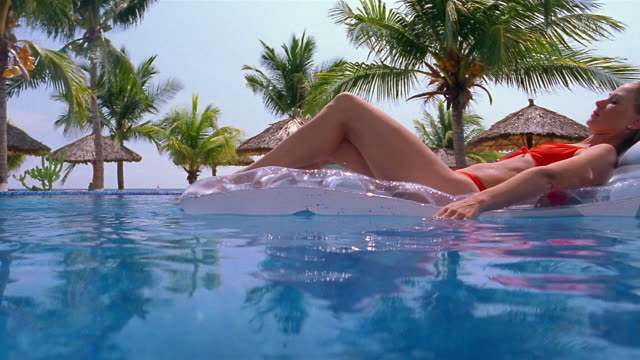 Low angle wide shot woman floating past CAM on raft in pool with palm trees in background