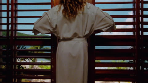 vídeos y material grabado en eventos de stock de low angle wide shot woman opening double doors and walking onto balcony / looking at beach - hotel de lujo