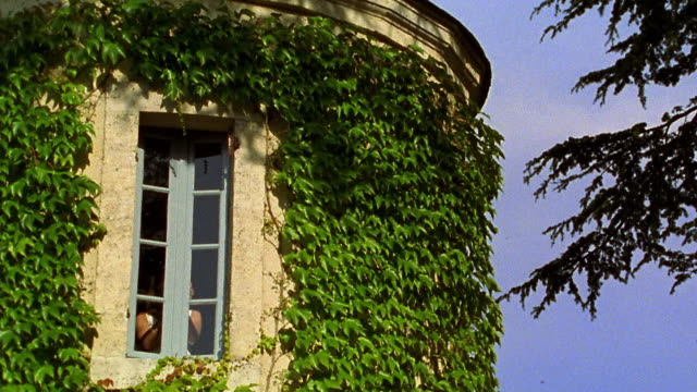 vídeos de stock e filmes b-roll de low angle wide shot woman opening window of chateau / france - janela aberta