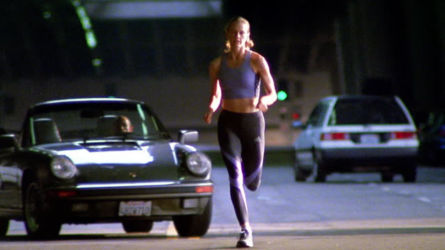 Low angle wide shot woman running towards camera on city street with car turning in background / Los Angeles