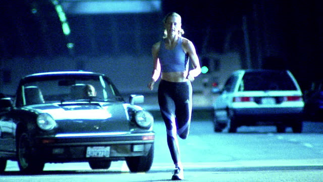 stockvideo's en b-roll-footage met low angle wide shot woman running towards camera on city street with car turning in background / los angeles - elasthaan