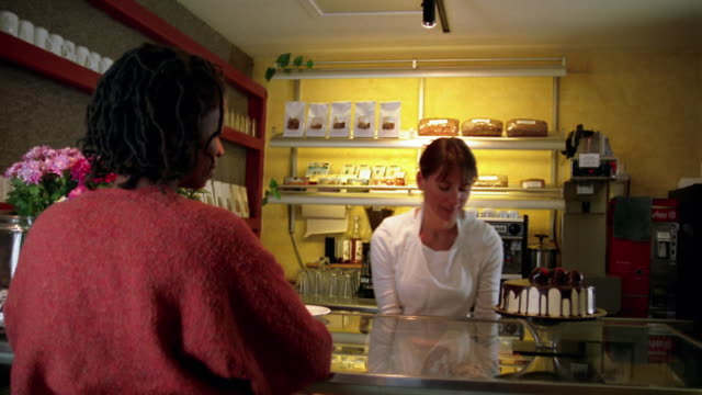 low angle wide shot woman serving croissant to customer in cafe / taking money - cream cake stock videos & royalty-free footage