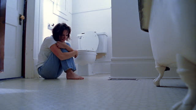 low angle wide shot woman sitting on floor of bathroom hugging knees to her chest near toilet - brechreiz stock-videos und b-roll-filmmaterial