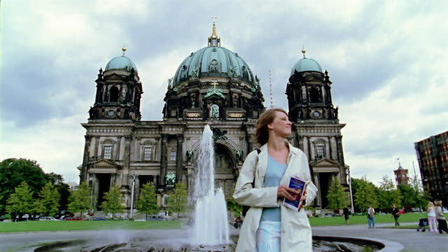 Low angle wide shot woman walking by fountain in front of Berlin Cathedral (Berliner Dom) / reading guidebook