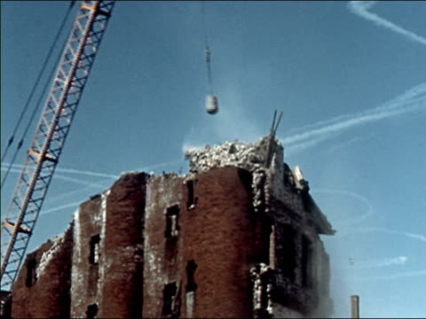 vidéos et rushes de 1956 low angle wide shot wrecking ball knocking down building - destruction