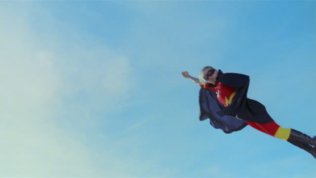 vídeos de stock, filmes e b-roll de low angle wide shot young blonde woman in mask, cape, and superhero costume in midair simulating flying after jumping on trampoline / las vegas, nevada - super herói