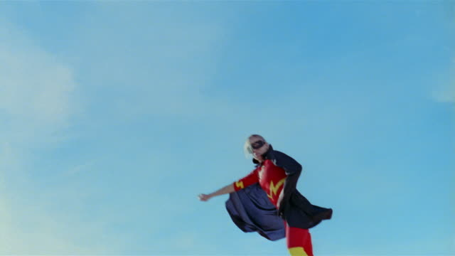 vidéos et rushes de low angle wide shot young blonde woman in mask, cape, and superhero costume in midair simulating flying after jumping on trampoline / las vegas, nevada - agilité entreprise