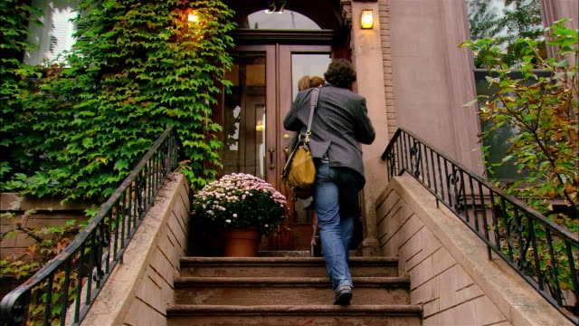 Low angle wide shot young couple entering brownstone building/ Brooklyn, New York