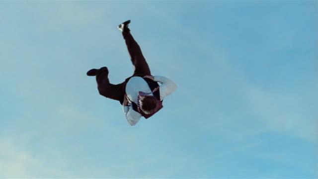 vídeos de stock e filmes b-roll de low angle wide shot young man in heavy businessman costume jumps on trampoline and does mid-air cartwheel / las vegas, nevada - trampolim equipamento desportivo
