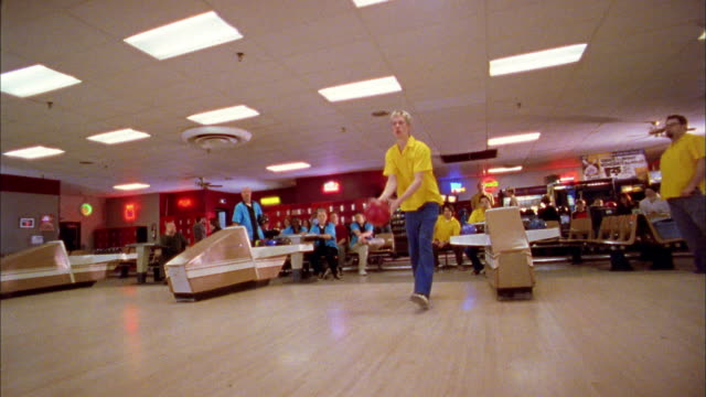 low angle wide shot young man stepping to lane and releasing bowling ball - bowling ball stock videos & royalty-free footage