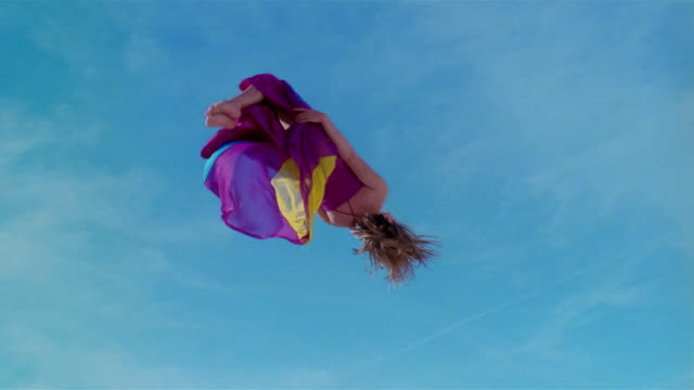 low angle wide shot young woman in colorful dress jumping on trampoline and doing backflip / las vegas, nevada - jumping stock videos & royalty-free footage