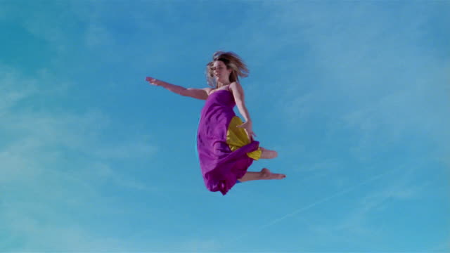 Low angle wide shot young woman in colorful dress jumping on trampoline, kicking legs up, and spinning around / Las Vegas, Nevada