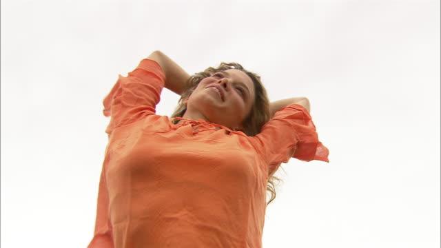 vídeos y material grabado en eventos de stock de low angle wide shot young woman stretching and smiling/ woman folding arms across stomach/ umbria - seno