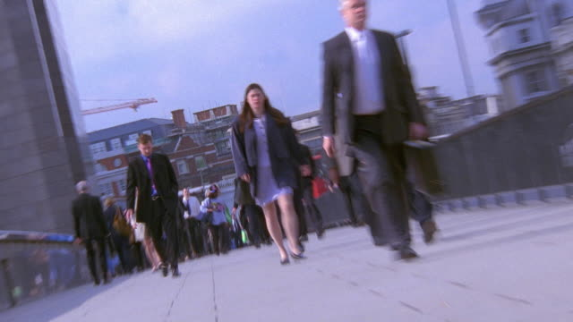 FAST MOTION low angle wide shot zoom in business crowds walking on sidewalk during rush hour in background / London