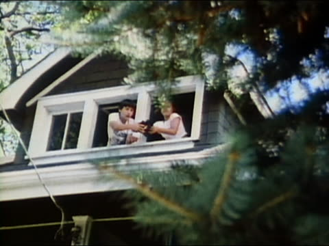 1986 low angle wide shot zoom in girl and boy looking out from window through binoculars / pointing + smiling / audio - osservare gli uccelli video stock e b–roll