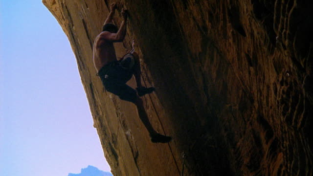 low angle wide shot zoom out rock climber with safety lines climbing up inverted rock face / nevada - ロッククライミング点の映像素材/bロール