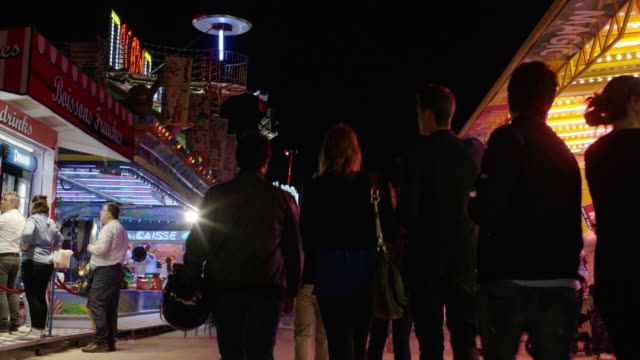 low angle wide time lapse shot of crowd at carnival / paris, france - fairground stall stock videos & royalty-free footage