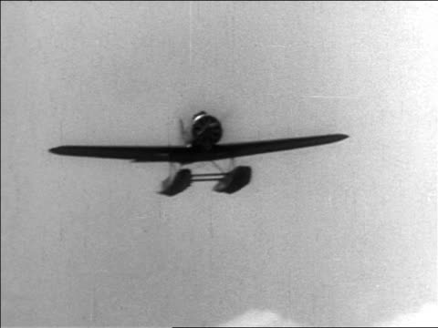 vidéos et rushes de b/w 1935 low angle will rogers' illfated hydroplane flying over camera outdoors / documentary - 1935