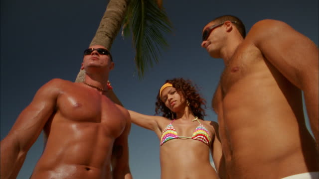 vídeos y material grabado en eventos de stock de low angle woman and two barechested men looking seriously at cam - mujer con grupo de hombres