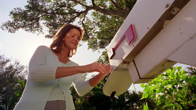 low angle MS woman getting mail out of mail box + looking pleased